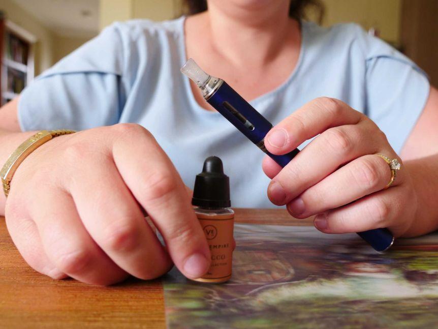 A close up of a woman holding a vape and a bottle of vape liquid